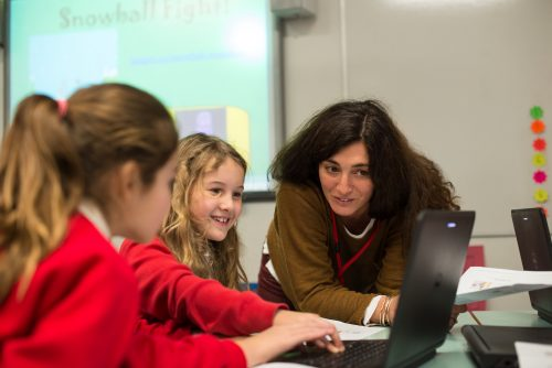 Two girls being taught about computing by a woman