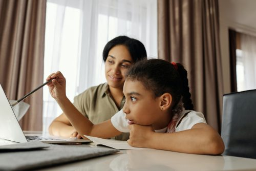 A girl and mother doing a homeschooling lesson at a laptop