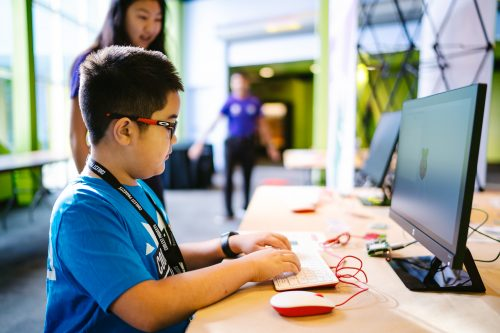 A boy using a Raspberry Pi desktop computer