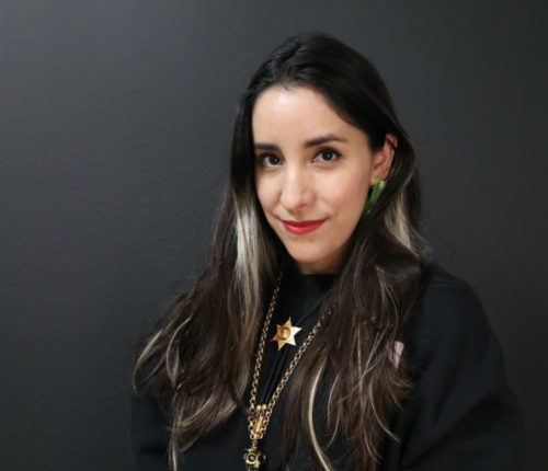 Estefannie in a black top with long black hair and gold necklaces