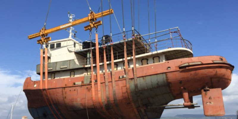 restored boat being pulled out of water before any work had been done on it